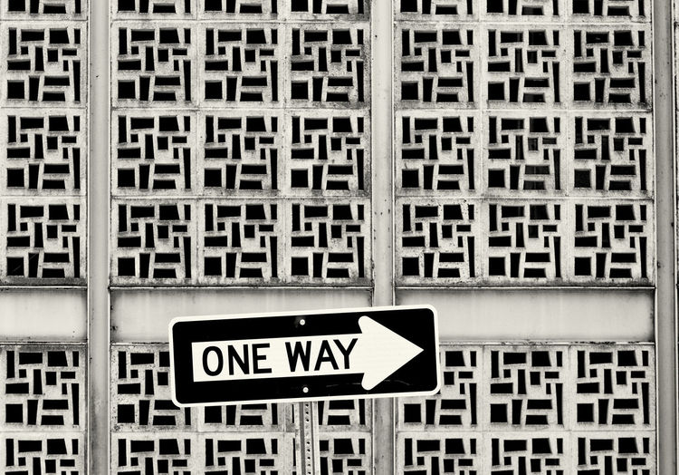 One Way Sign Against Patterned Wall