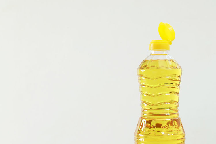 Close-up of yellow glass bottle against white background
