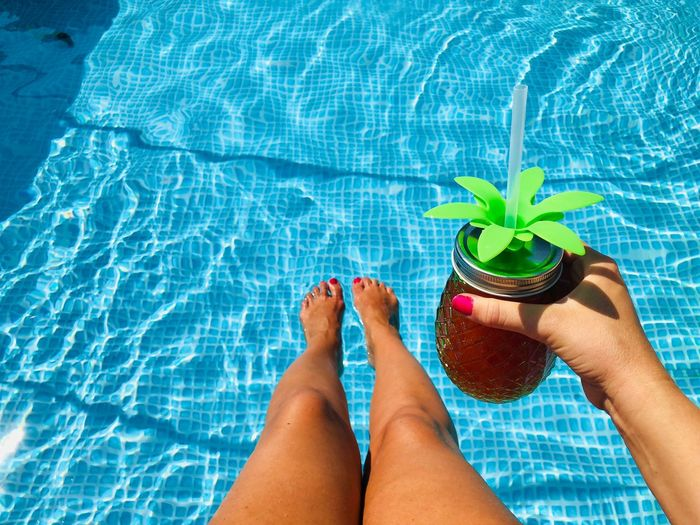 Low section of woman with drink in swimming pool