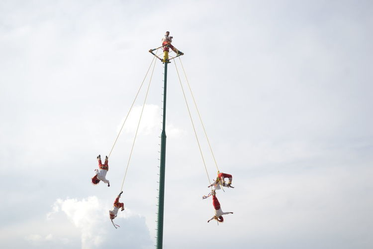 Low angle view of people hanging on ropes against sky