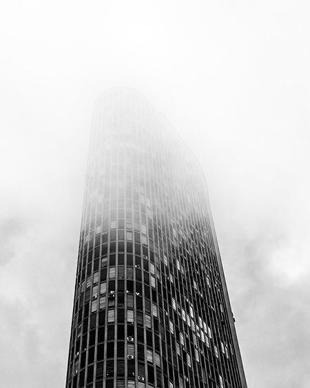 Low angle view of skyscraper against sky during foggy weather