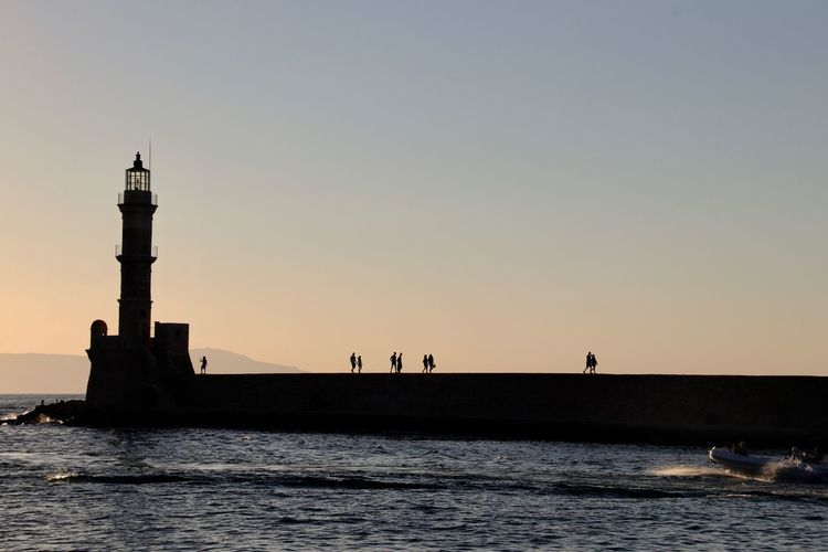 Silhouette people walking on pier towards lighthouse during sunset