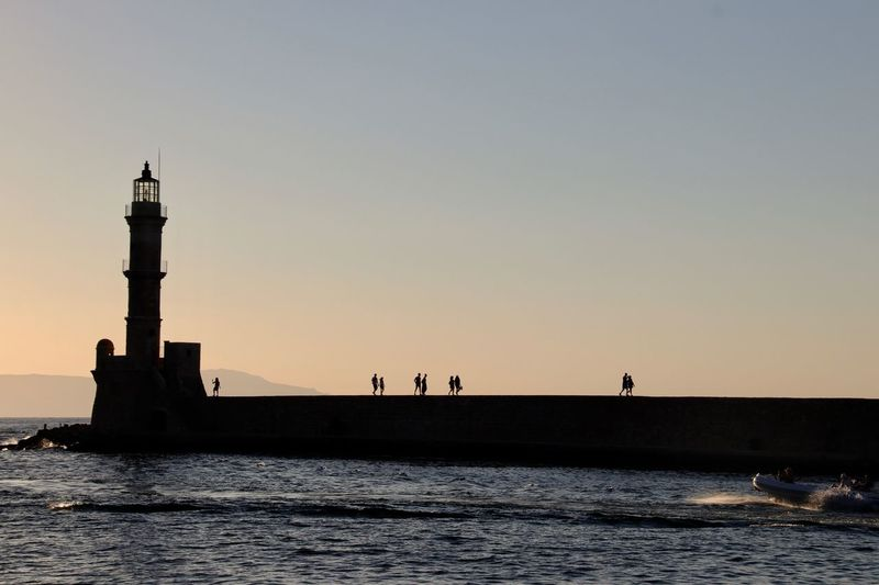 Chania Crete Greece Harbour Architecture Beauty In Nature Building Building Exterior Built Structure Clear Sky Copy Space Group Of People Guidance Lighthouse Nature Orange Color Outdoors Scenics - Nature Sea Silhouette Sky Sunset Sunsetting On Water Tower Water Waterfront