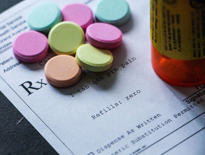High angle view of colorful pills and prescription