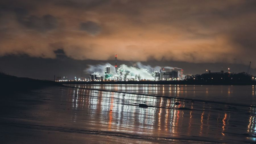 Illuminated factory by river against cloudy sky at night