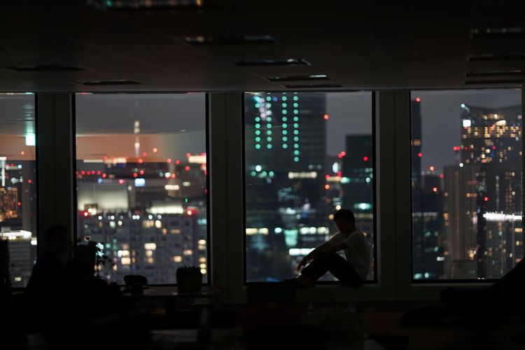 People sitting in illuminated building at night