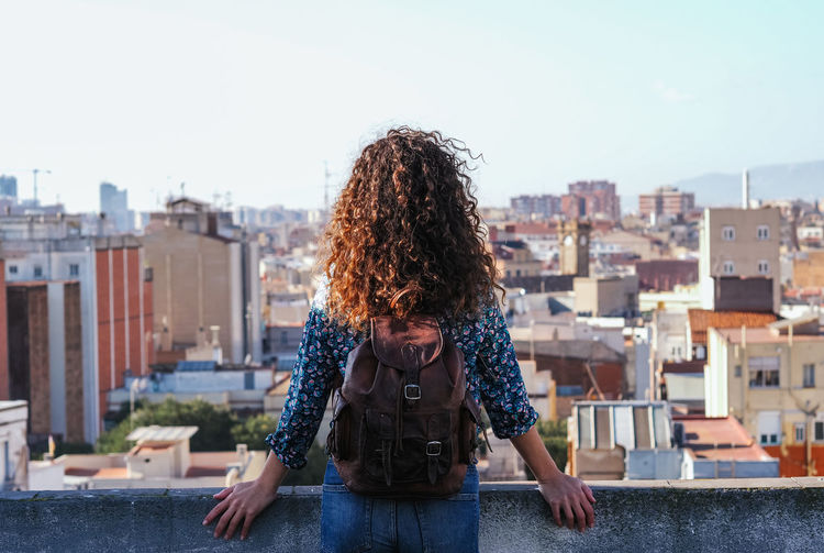 Woman standing against buildings in city against sky