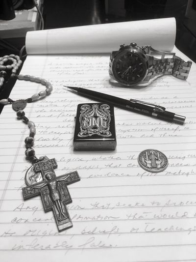 """Six Important Possessions other than my Cameras and library of books. I carry a Zippo lighter (though I'm a non-smoker) with the word """"King"""" inscribed upon it. It serves as a visual reminder to conduct myself as a king at all times. The mechanical pencil, Pentel 0.5, black, has been a constant companion through many years and many of my musings. The watch, a Citizen World Timepiece, was given to me by my wife. I treasure it for sentimental reasons as well as value it for its aesthetic appeal and functionality. I keep a St. Francis rosary, though I'm not Catholic, as a reminder of my Christian faith and duties. Also, I carry a St. Benedict coin in my wallet as reminder that evil is real and spiritual protection is always needed. And last a pad of paper which serves as my canvas for my drawings, poetry, drawings, ideas, lyrics, and writings. Personal Possessions Meaningfulpossessions"""