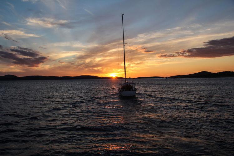 Sailboat in sea at sunset
