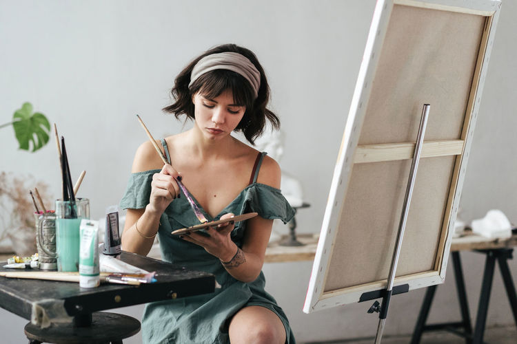 Young woman painting on canvas while sitting on table