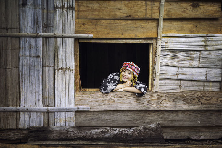 Smiling woman peeking through window of wooden house