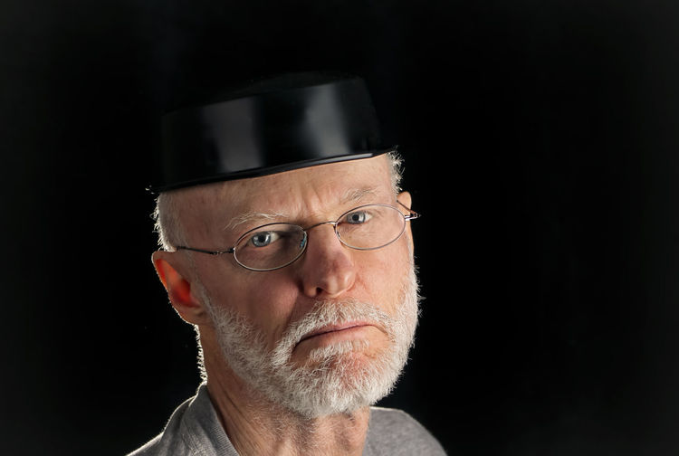 Portrait Of Man Wearing Funny Hat Against Black Background
