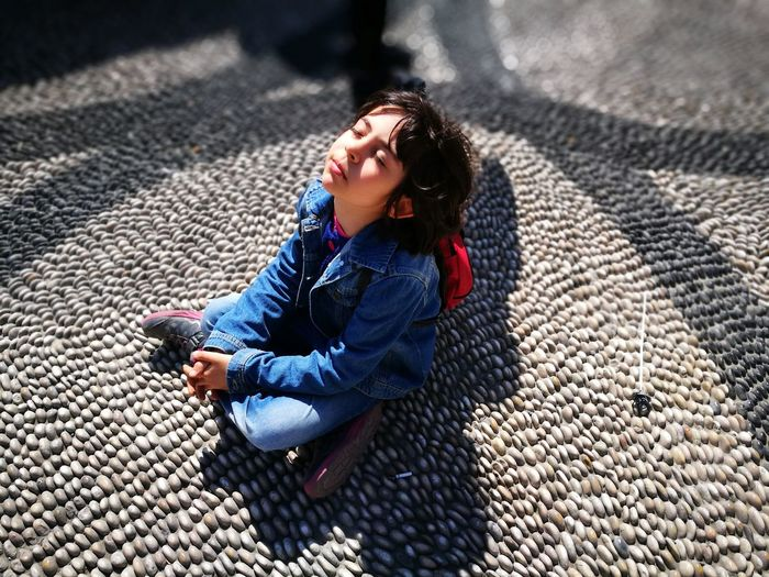 High Angle View Of Girl Sitting On Footpath