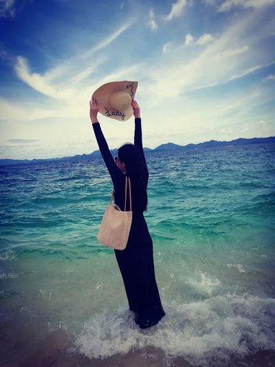 Woman holding hat while standing in sea against sky