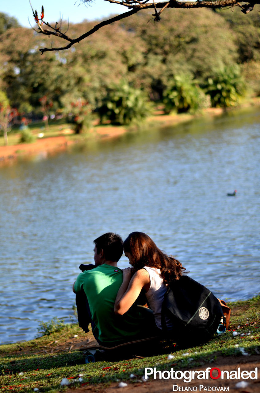 water, two people, real people, togetherness, rear view, lake, leisure activity, nature, love, women, day, lifestyles, outdoors, sitting, tree, bonding, men, beauty in nature, couple - relationship, vacations, full length, young women, young adult, adult, people