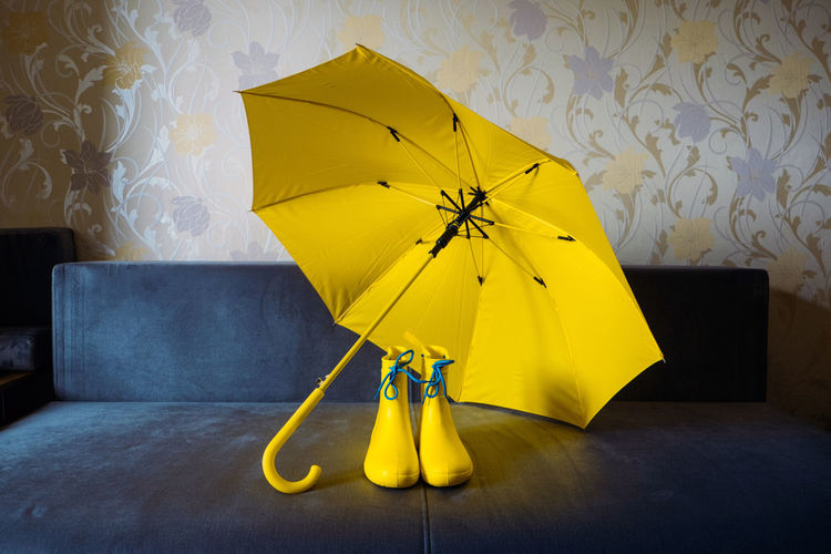 Yellow umbrella on wet table at home