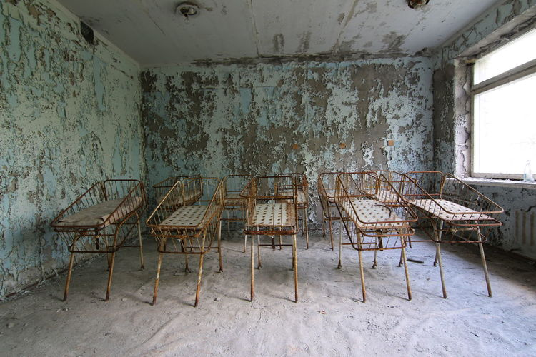 Old cribs against wall in abandoned hospital