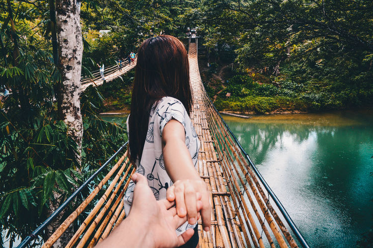 Cropped hand of man holding woman on bamboo footbridge over river in forest