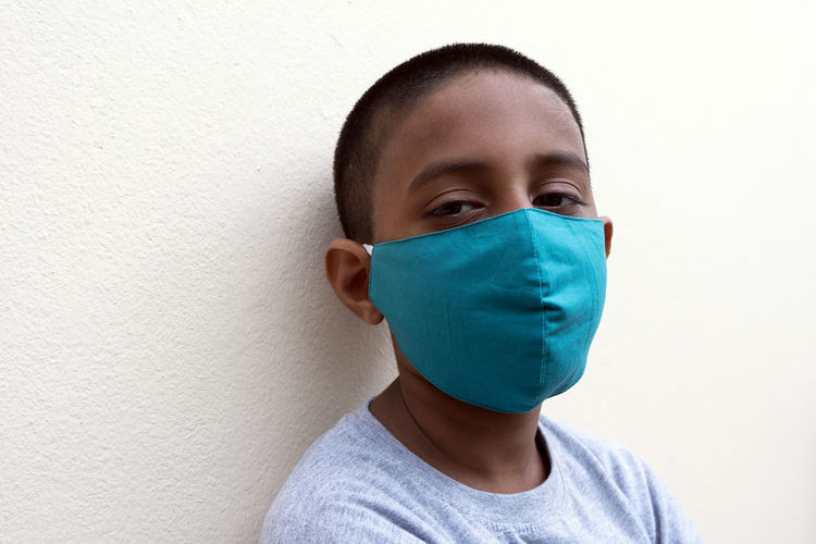 Portrait of boy wearing mask against white wall