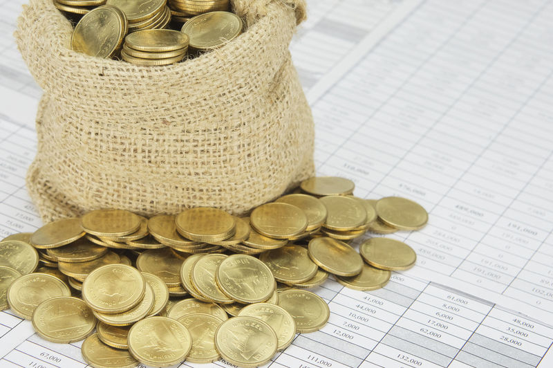 Close up stack of gold coins with brown sack of coins on finance account. Business Gold Stack Work Account Bag Balance Brown Coin Concept Currency Document Finance Invest Paper Paperwork Pile Receipt Report Sack Savings Success Wealth White Workload