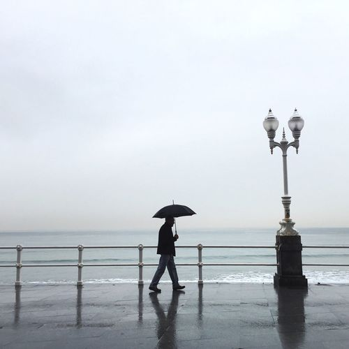 Side View Of Man Walking Under Umbrella During Rainfall By Sea Against Sky