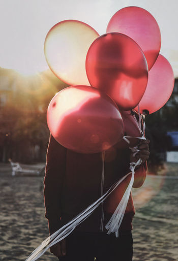 Close-up of red balloons in lake against sky