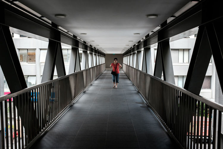 Rear view of man walking on bridge