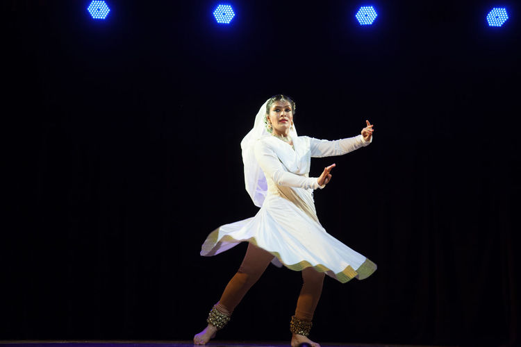 Low angle view of man dancing against black background