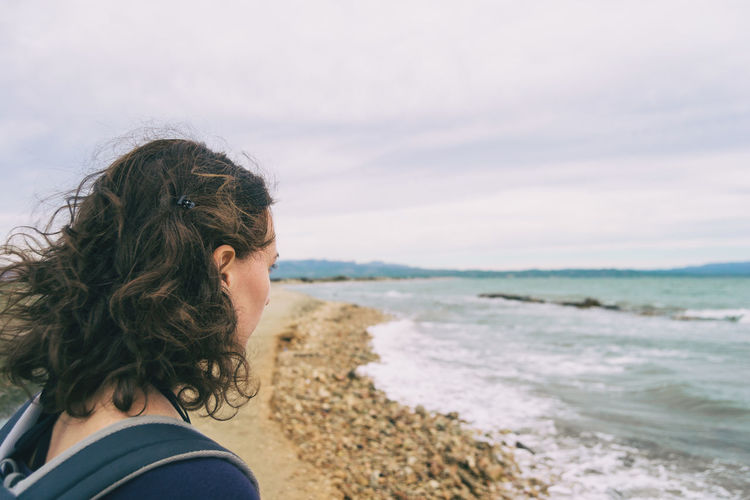 Portrait of woman looking at sea against sky