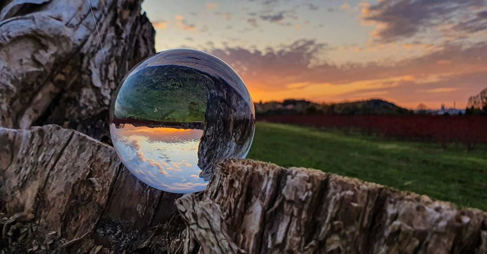 Close-up of crystal ball on landscape against sky at sunset