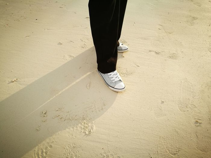 Low section of person standing on sand