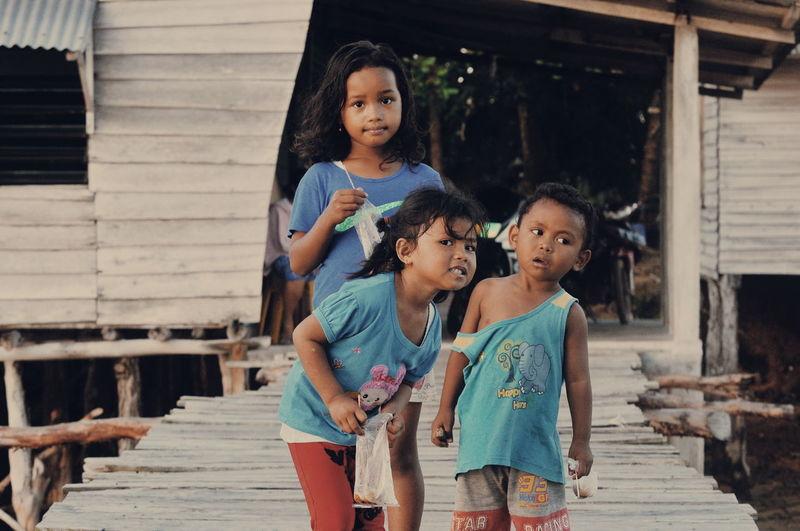 Siblings standing on boardwalk