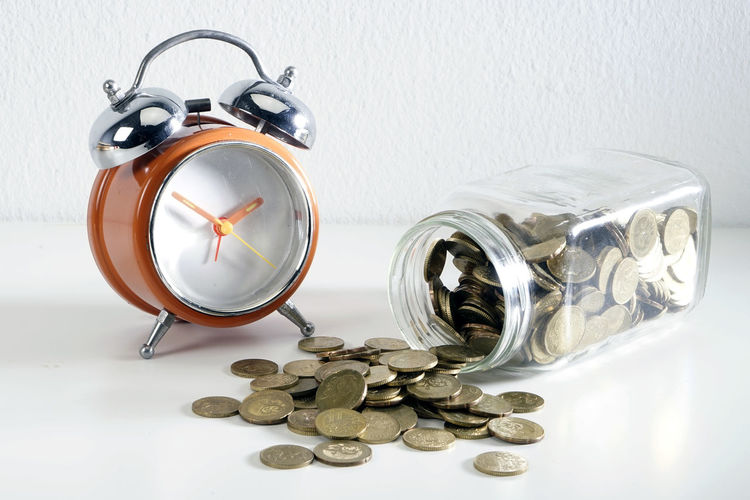 Still Life Indoors  Table Container Clock No People Jar Alarm Clock Glass - Material Metal Large Group Of Objects Time Transparent Finance Close-up Coin Shape Abundance Wealth