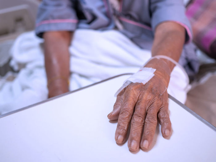 Saline solution drip on old women hand in hospital. health care and medical equipment concept.