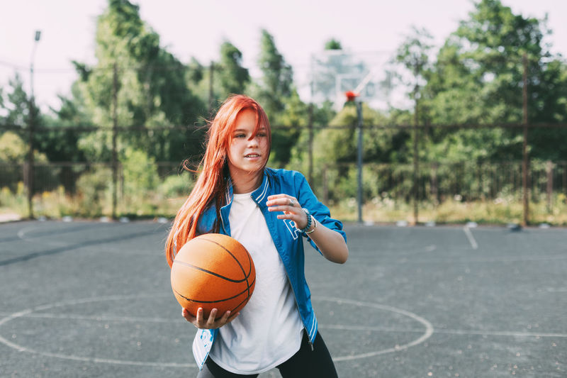 A young basketball player is training on an outdoor basketball court, a teenage girl is playing