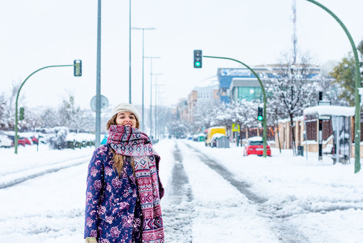 Woman on snow covered street in city during winter