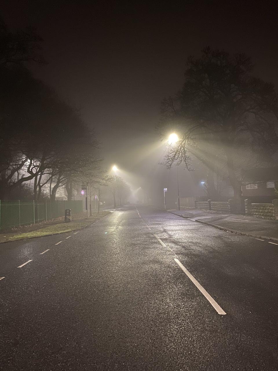 EMPTY ROAD BY ILLUMINATED STREET LIGHT AT NIGHT
