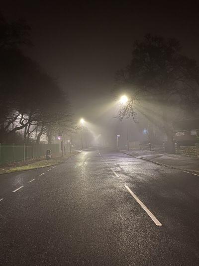 Empty road by illuminated city at night