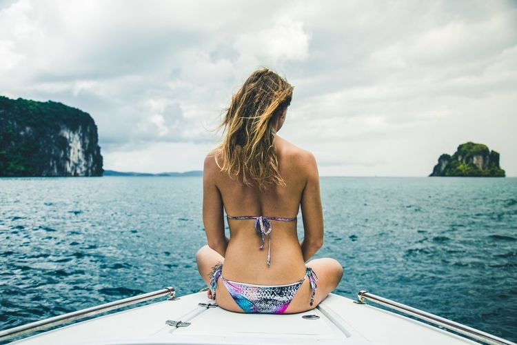 Rear view of young woman sitting by sea against sky