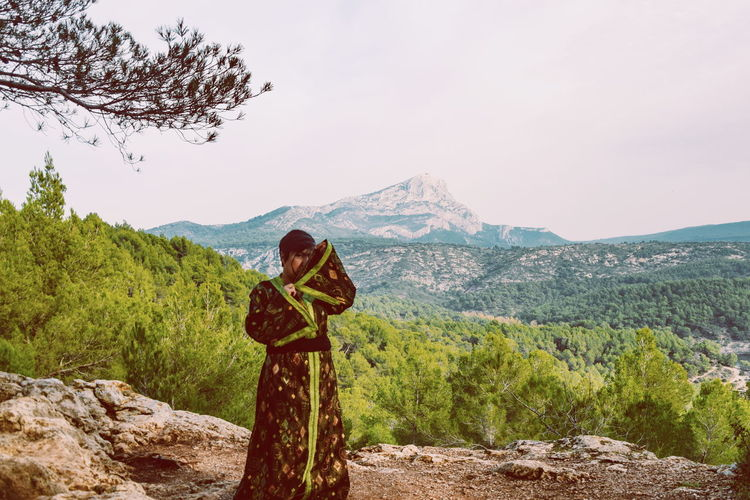 Woman wearing kimono while standing on mountain against sky