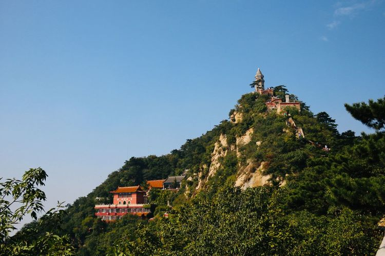 Traditional building on mountain against clear blue sky