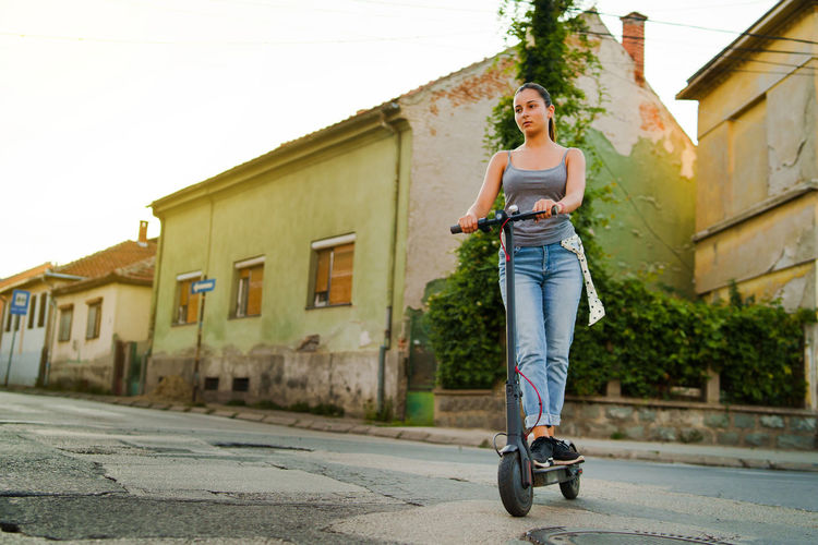 Woman riding motorcycle on street against building