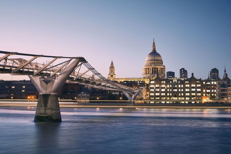 London cityscape at dusk. city waterfront with millennium footbridge against st. pauls cathedral.