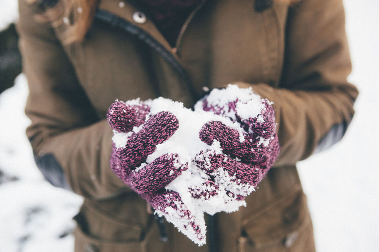Close-up of female hands holding snow