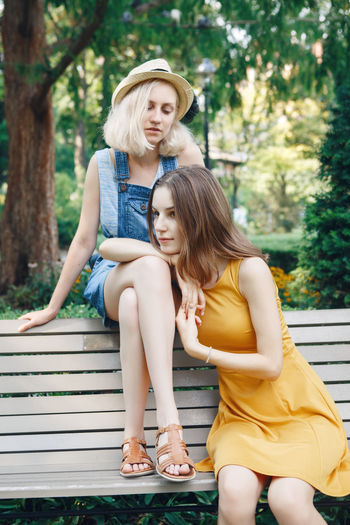 Female friends sitting on bench at park