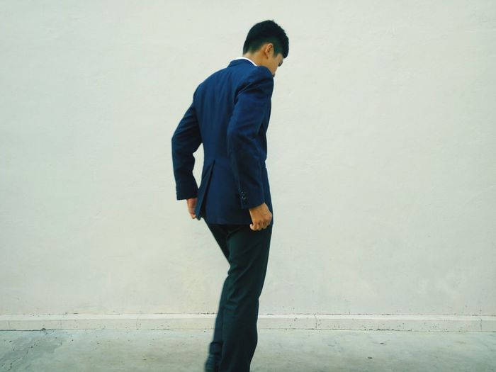 Side view of young man in suit standing against wall