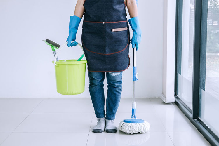 Low section of woman with cleaning equipment standing at home