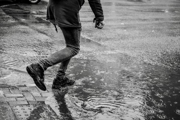 Low section of man running on wet road