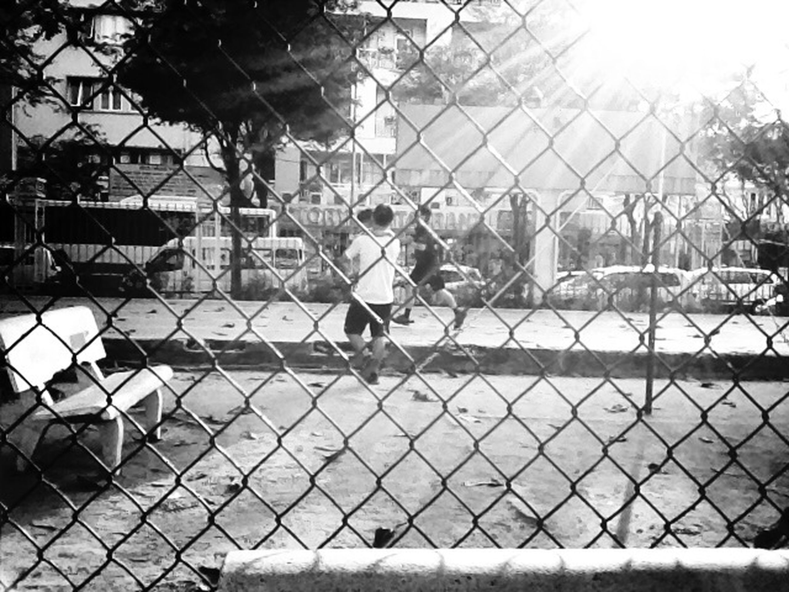 chainlink fence, fence, protection, park - man made space, metal, lifestyles, sunlight, safety, childhood, playground, leisure activity, day, tree, outdoors, focus on foreground, incidental people, shadow, street