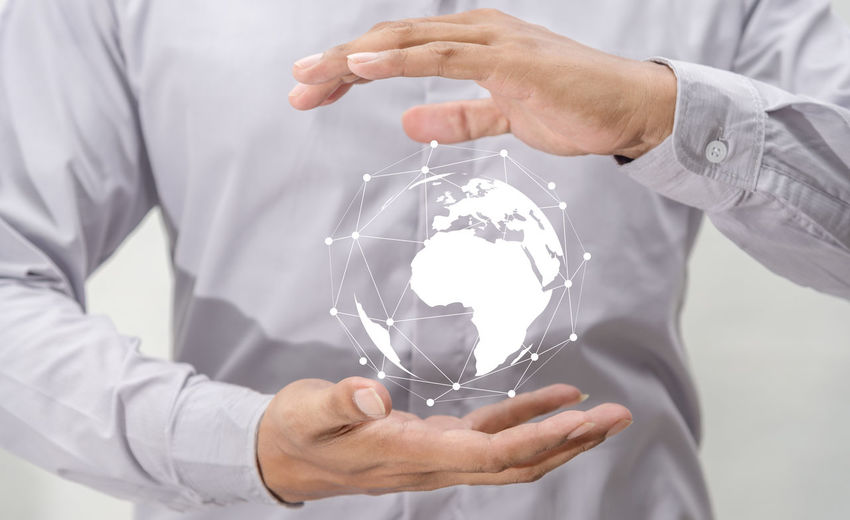 Midsection of man holding illustrative globe